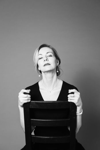 Portrait of mature woman sitting against wall