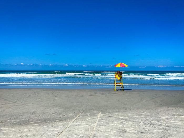 Full length of man on beach against blue sky