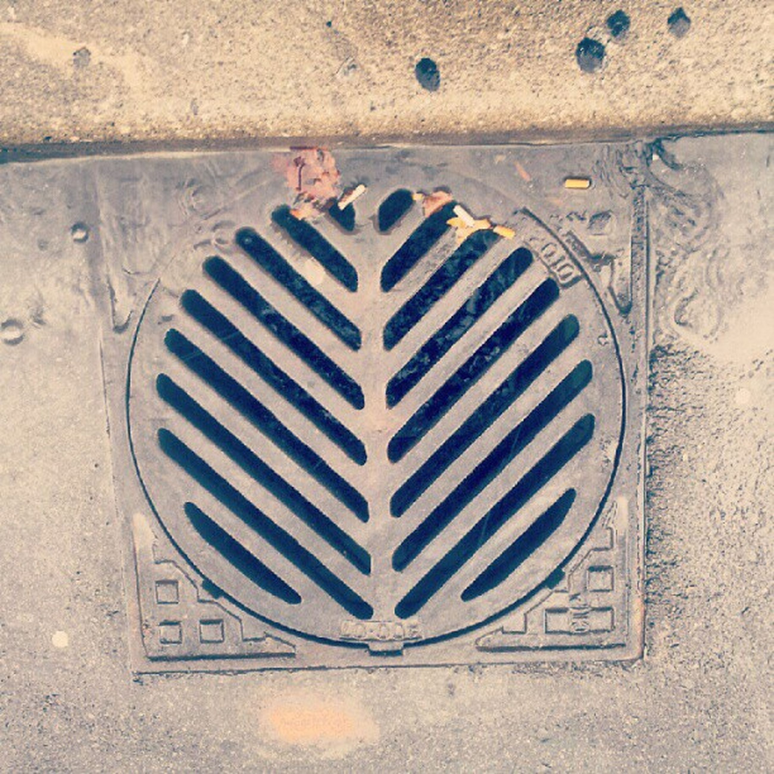 wall - building feature, built structure, pattern, architecture, textured, high angle view, close-up, wall, circle, no people, metal, old, geometric shape, day, communication, street, white color, outdoors, manhole, shape