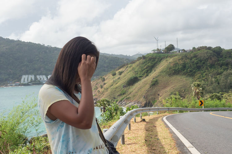 Young woman on road against mountain range