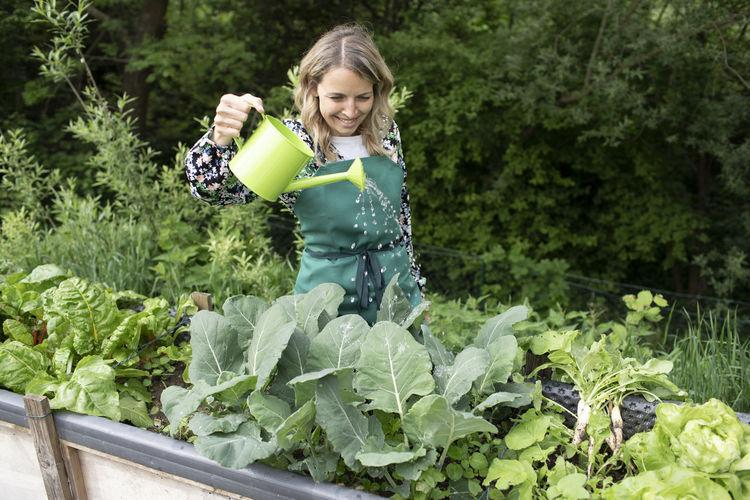 Smiling woman holding fresh green plants