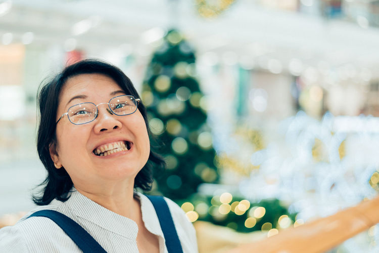 Portrait Of Smiling Woman Against Christmas Tree In Shopping Mall