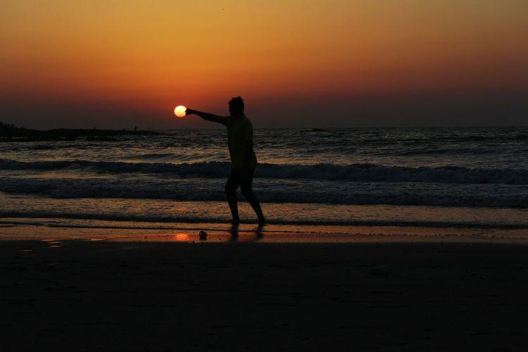 Optical Illusion Of Silhouette Man Punching Sun At Beach