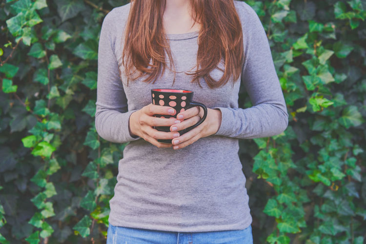 Midsection of woman holding coffee cup while standing against plants