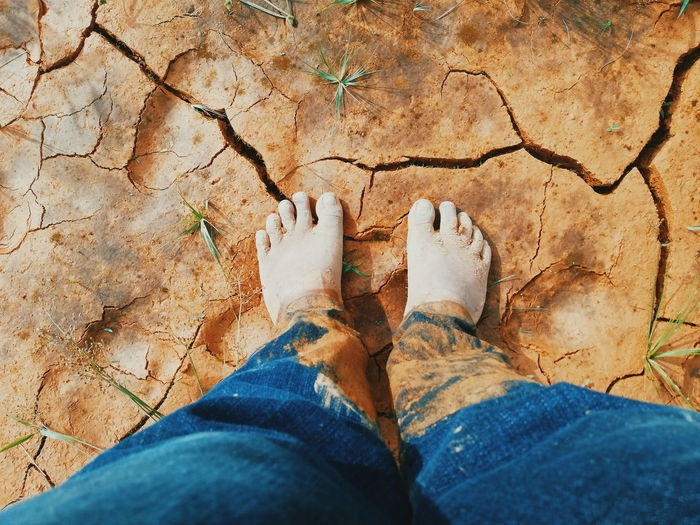Low section of man standing with muddy jeans on cracked field