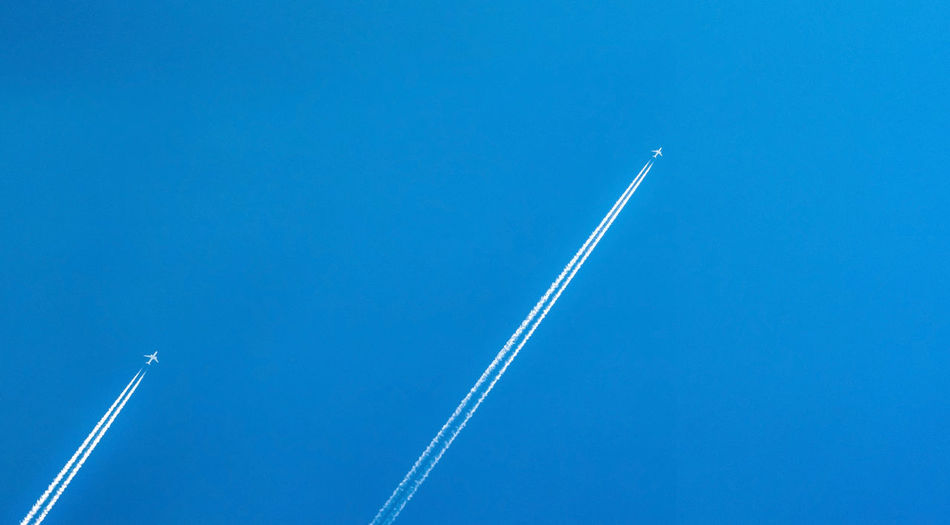 Airplane with white condensation tracks. jet plane on clear blue sky with vapor trail. travel