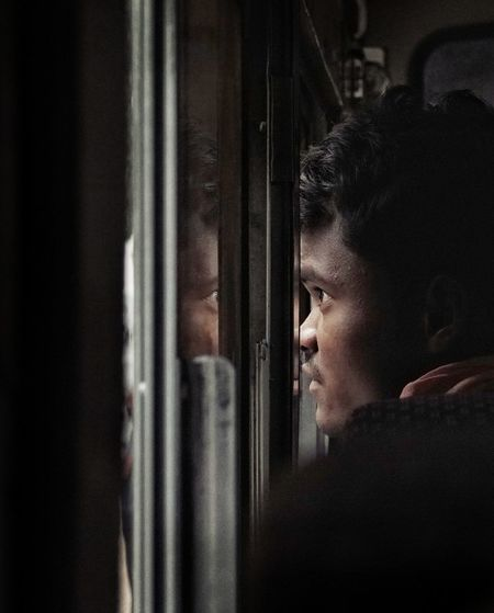 Side View Of Mid Adult Man Looking At Window In Train