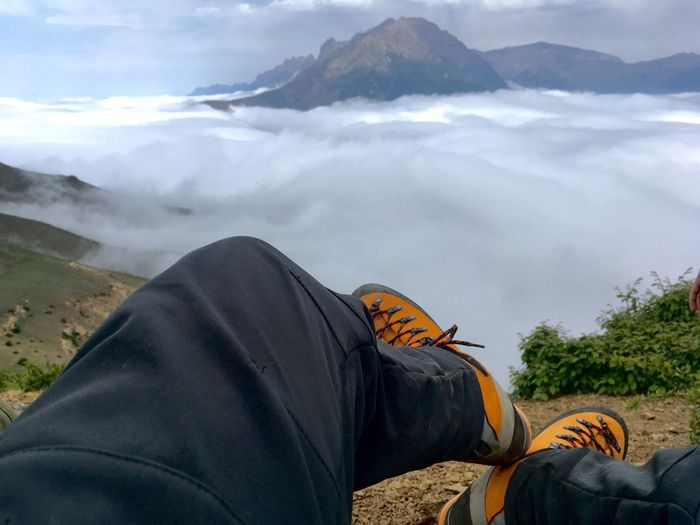 Low section of man sitting on mountain against cloudy sky