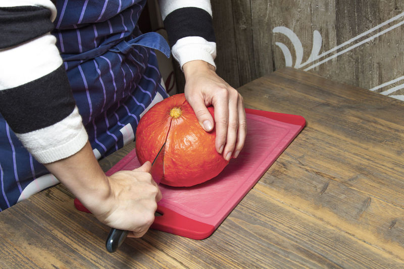 Midsection of woman holding apple on table