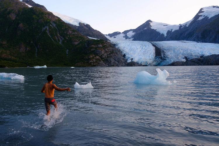 Man swimming in lake against mountain