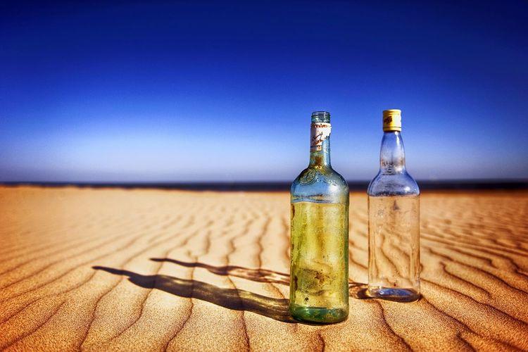 Bottles on sandy beach against clear blue sky