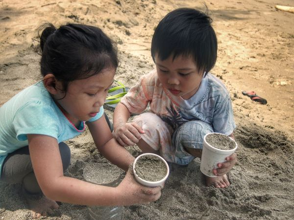 Kids playing with a sand at the beach Child Boys Two People Togetherness Childhood Children Only Friendship Leisure Activity Heat - Temperature Looking Down Outdoors Girls Day sand Enjoying Beach