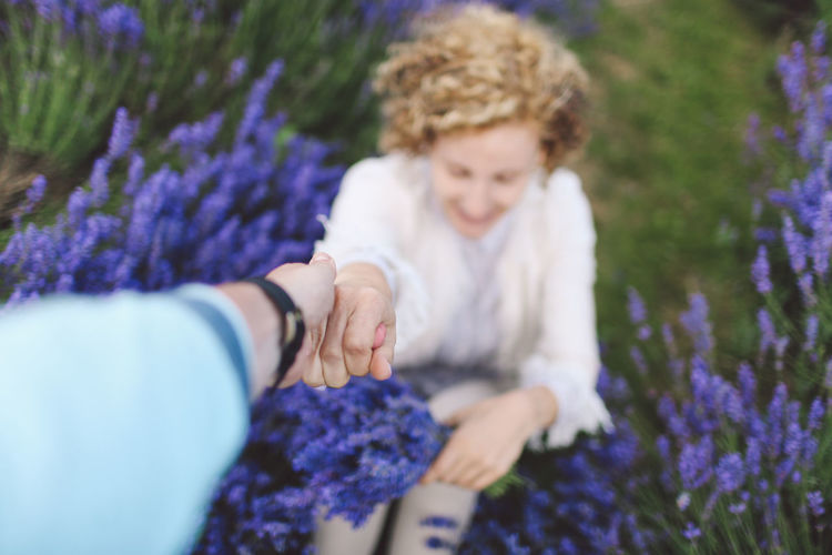 Cropped Image Of Person Holding Woman Hand At Lavender Field