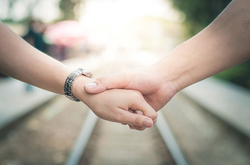 Cropped Image Of Couple Holding Hands Above Railroad Tracks