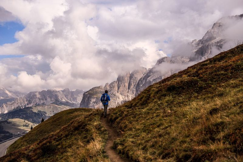 Rear view of man hiking on mountain against cloudy sky