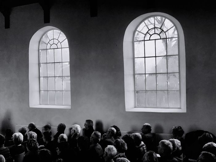 Group of people by windows and wall