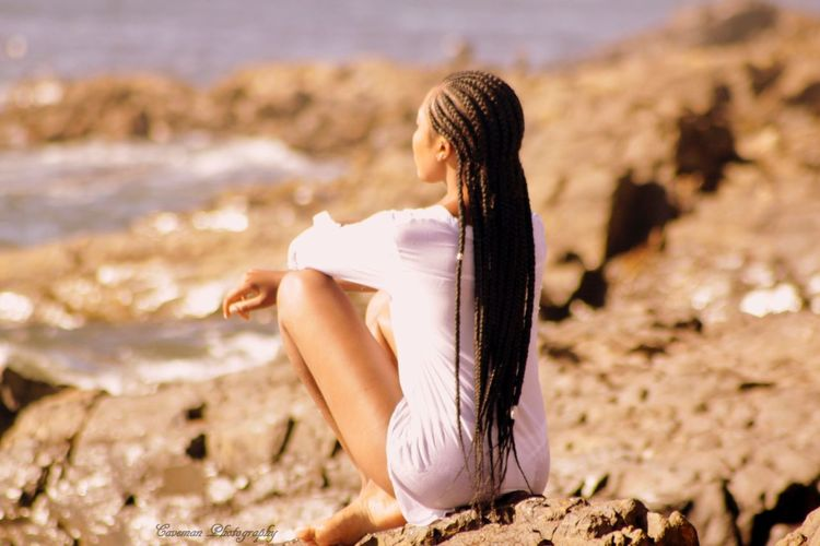 Woman With Dreadlocks Sitting At Beach During Summer