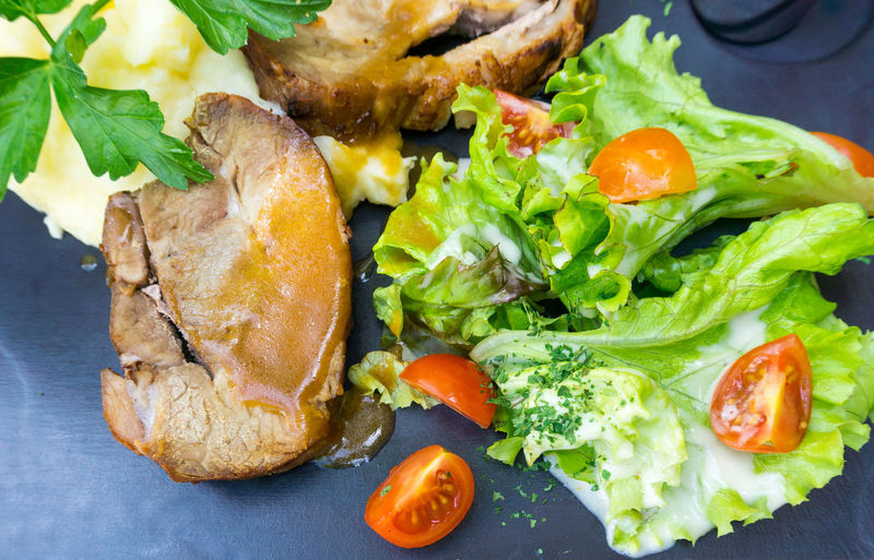 High Angle View Of Tomatoes And Lettuce With Pork On Table