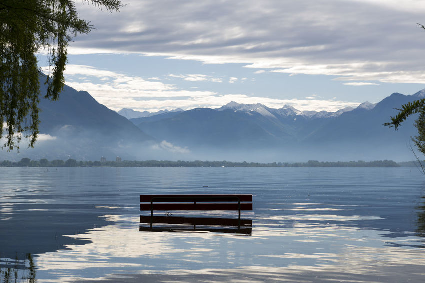 Bench on a flooding alpine lake Maggiore with mountain in Ticino, Switzerland. Alpine Lakes Wilderness Beauty In Nature Bench Cloud - Sky Day Flood Flooding Idyllic Lago Maggiore Lake Landscape Majestic Mountain Mountain Range Nature No People Outdoors Rear View Reflection Scenics Snowcapped Mountain Swiss Alps Tranquility Water Weather