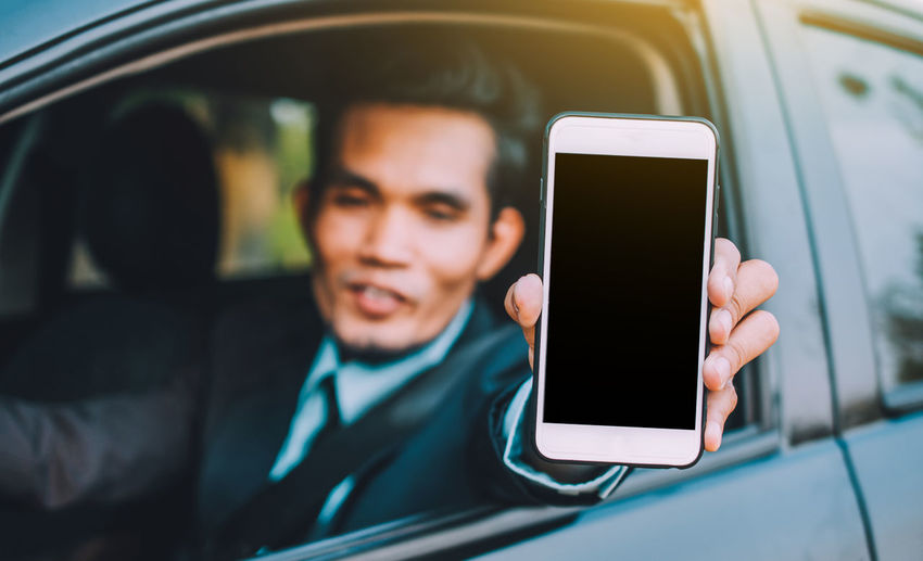 Businessman showing mobile phone while sitting in car