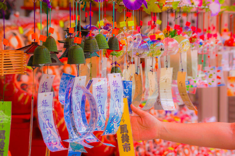 Cropped hand of woman holding decoration at market stall