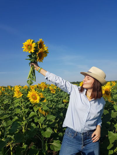 Beautiful woman holding sunflower on field against sky