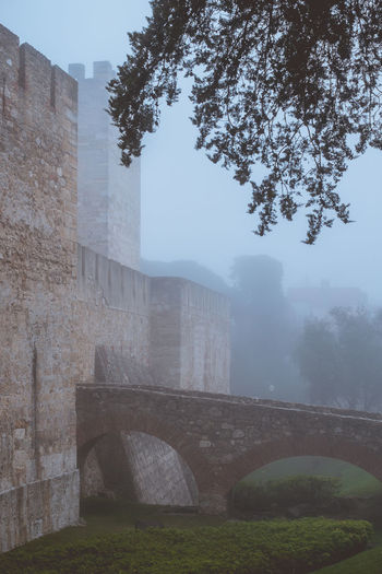 Medieval castle with the stone bridge during a foggy morning. Built Structure Architecture Building Exterior Plant The Past History Fog Tree Day Nature No People Outdoors Arch Sky Travel Destinations Old Building Bridge Tourism Arch Bridge Medieval Castle Serene