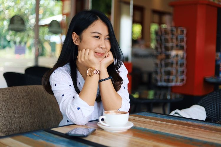 Sitting One Person Young Adult Women Smiling Adult Young Women Table Food And Drink Lifestyles Real People Indoors  Cup Drink Waist Up Hand On Chin Leisure Activity Beautiful Woman Casual Clothing Hair Hairstyle