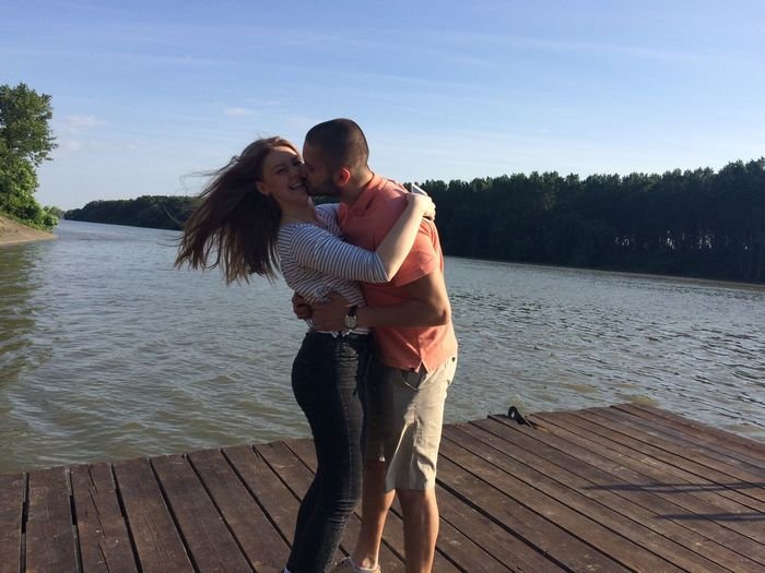 Man kissing woman while standing on jetty at lake