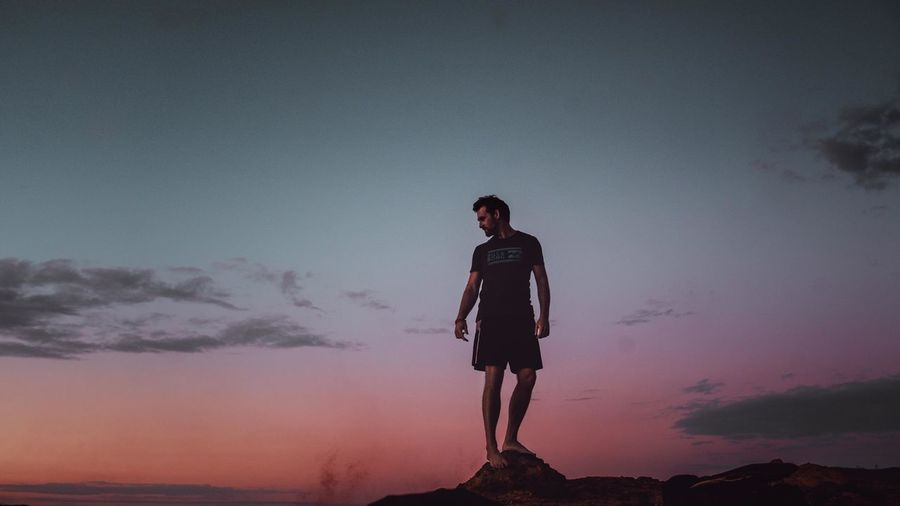 Full length of young woman standing against sky during sunset