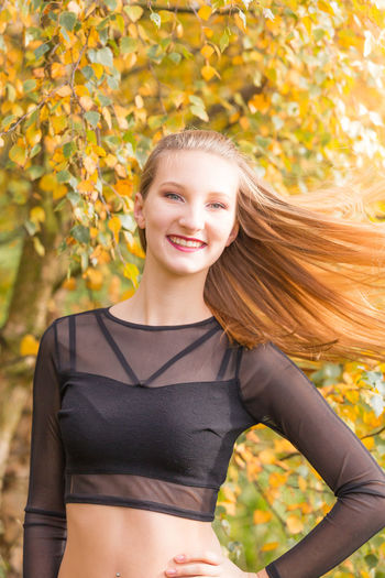 Portrait of young beautiful woman tossing her long blond hair while standing by autumn tree