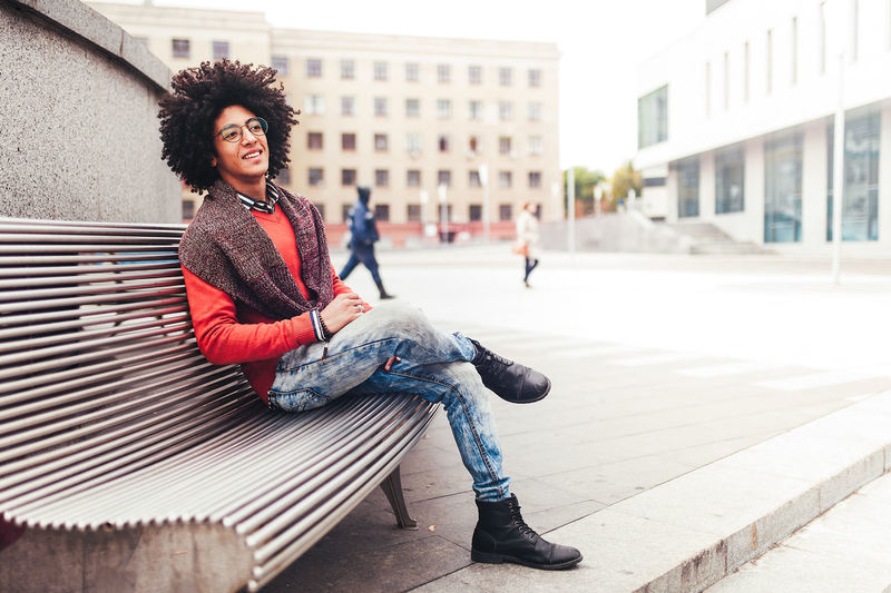Thoughtful young man smiling while sitting on bench in city