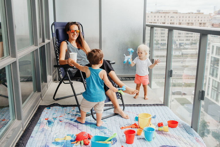 Young mother spending time together with children babies on balcony at home. staycation