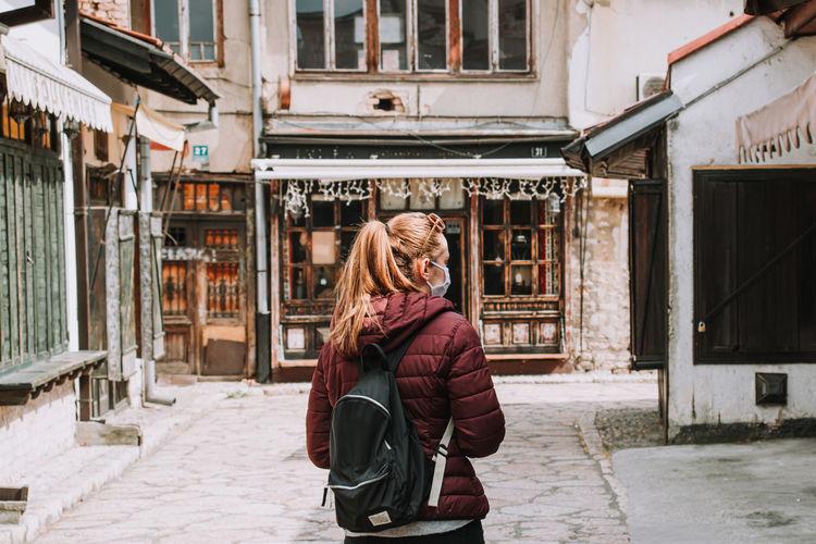 Full length of woman standing empty street due to coronavirus
