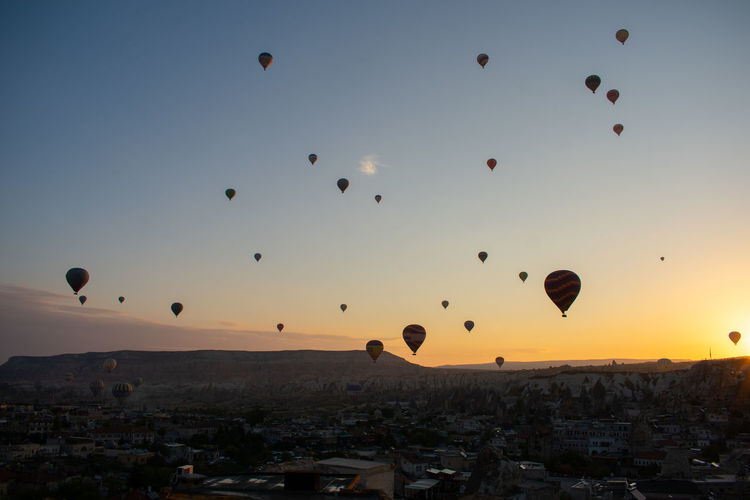Hot air balloons flying in city against sky during sunset