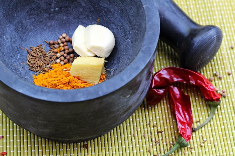High angle view of spices in mortar on mat