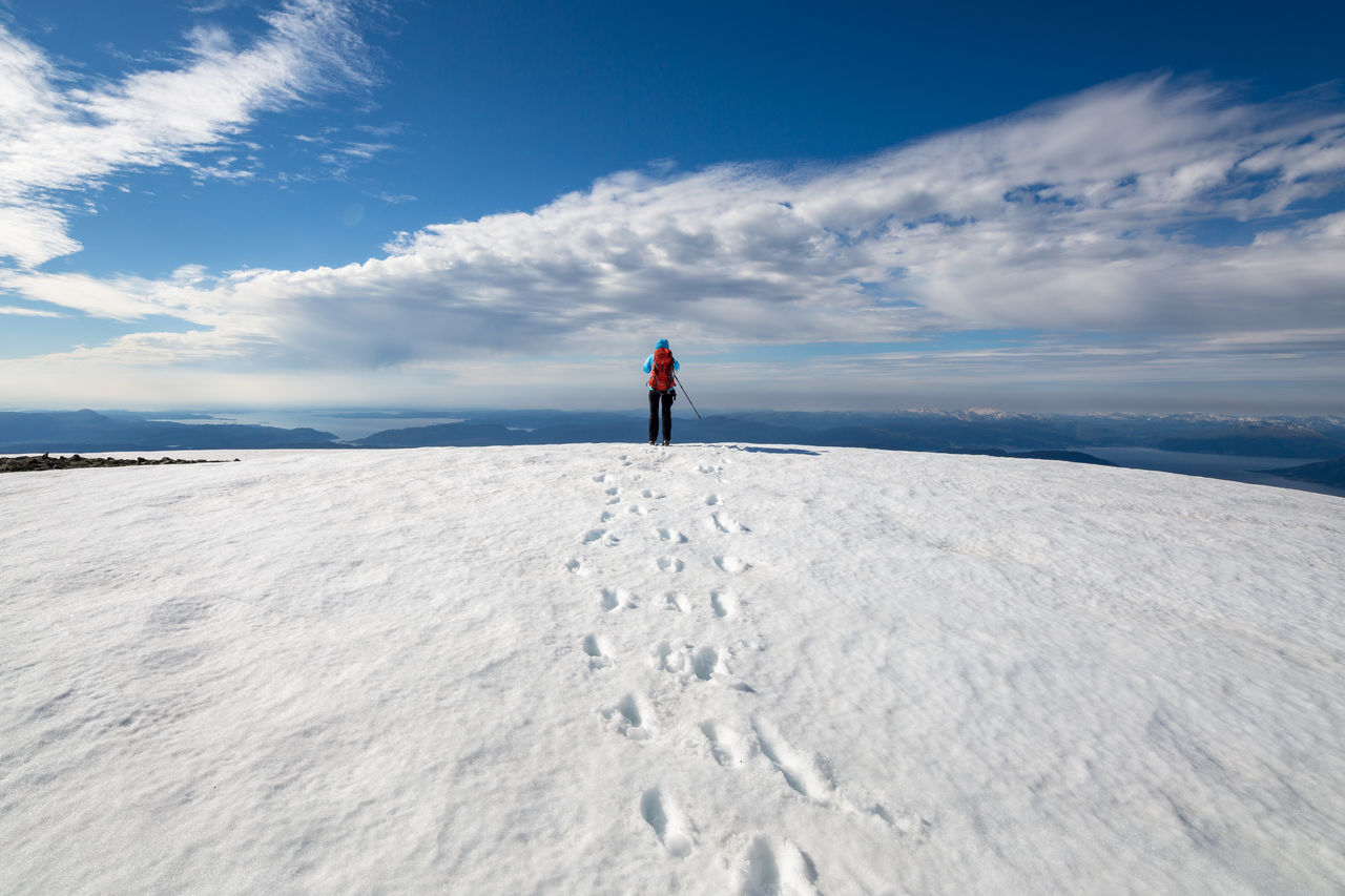 Person Hiking On Snow Covered Field Against Sky