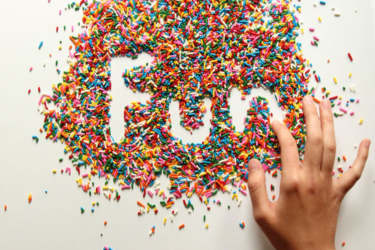 Cropped Hand Making Fun Text Amidst Colorful Sprinkles Over White Background