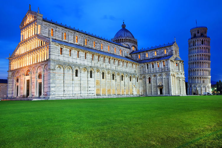 Illuminated pisa cathedral by leaning tower against blue sky at dusk