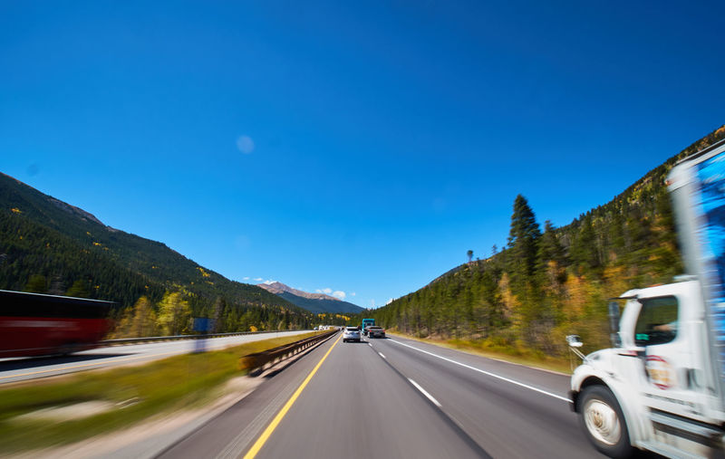 Transportation Road Motion Sky Blurred Motion The Way Forward Mountain Mode Of Transportation Motor Vehicle Direction Car Land Vehicle Speed Clear Sky Copy Space Blue Nature on the move Sign No People Mountain Range Outdoors Diminishing Perspective Road Trip Dividing Line