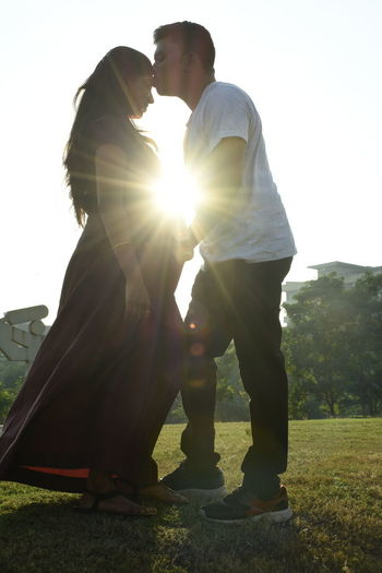 Side view of couple standing against sunlight