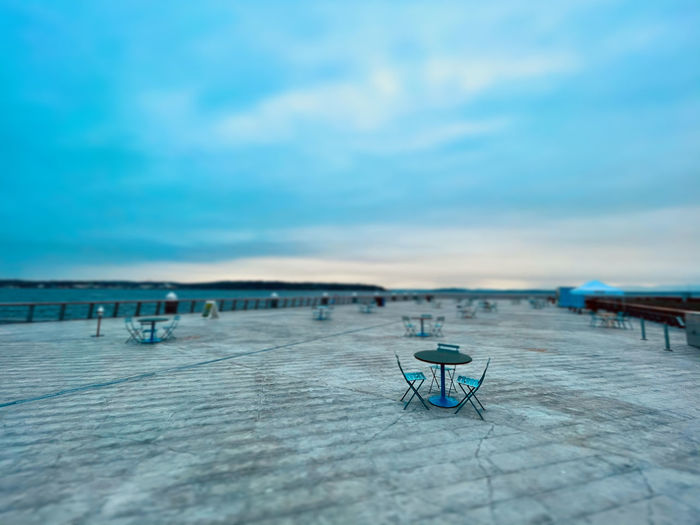 Empty chairs and tables against blue sky