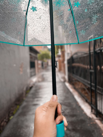 Midsection of woman holding umbrella during rainy season