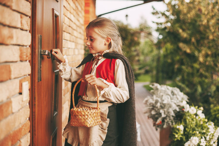 Little girl in a fairy costume with a basket in her hands is knocking on the door during