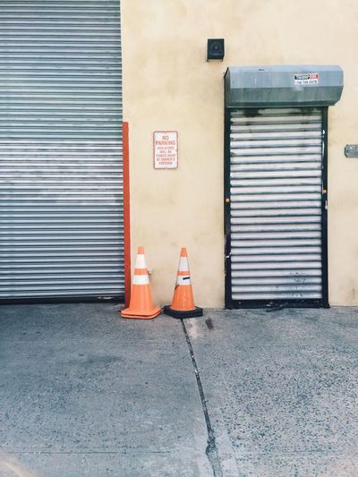 Traffic cones on sidewalk against garage