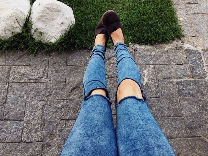 Low Section Of Woman Wearing Torn Jeans In Park