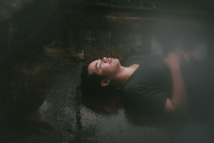 Portrait of young woman lying in water