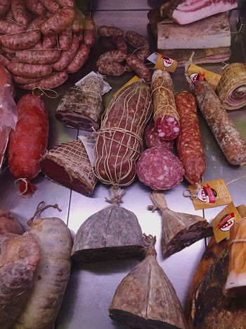 Italian meat products on display at a butcher's shop. Salumeria Italian Food Raw Food Freshness For Sale Retail  Market Variation Market Stall Choice Meat Shop Meat Close-up Display Sale Salami Group Of Objects Heap Repetition Charcuterie Sausage Prosciutto Small Business Business
