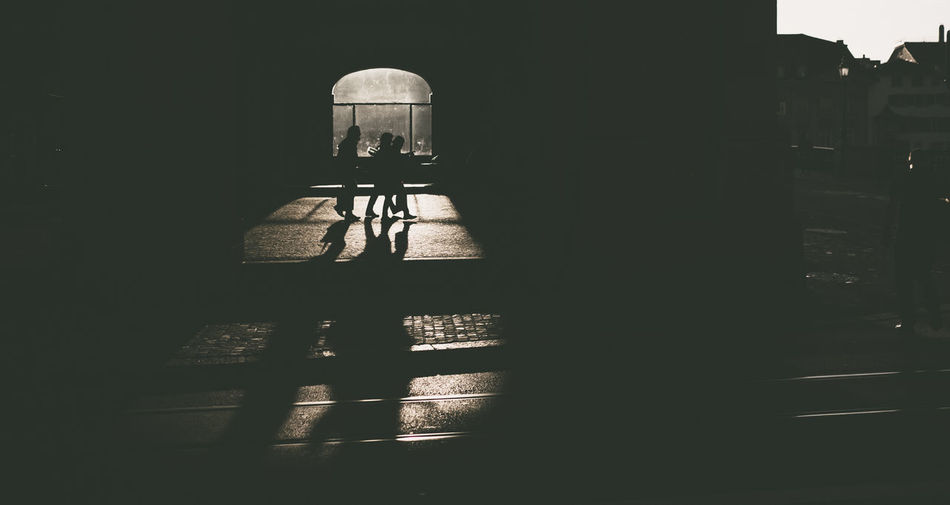 Silhouette people in illuminated building