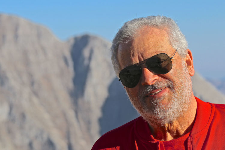 Close-up portrait of man wearing sunglasses against mountain